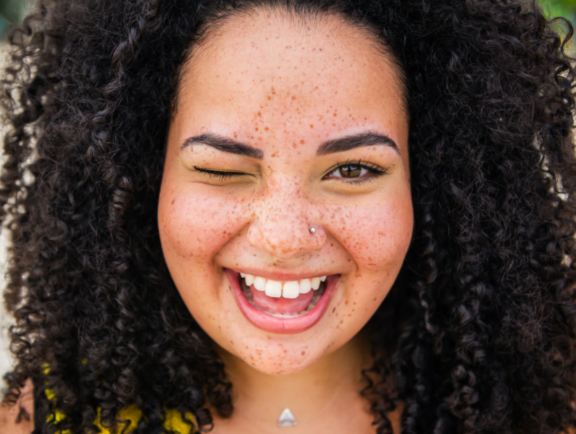 smiling girl with black curly hair